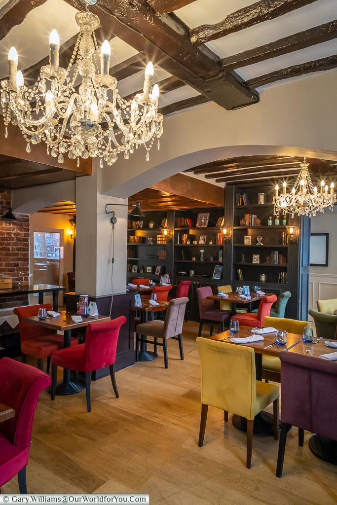 A view of the dining room, with its timber beams and elegant chandeliers lighting a contemporary restaurant.