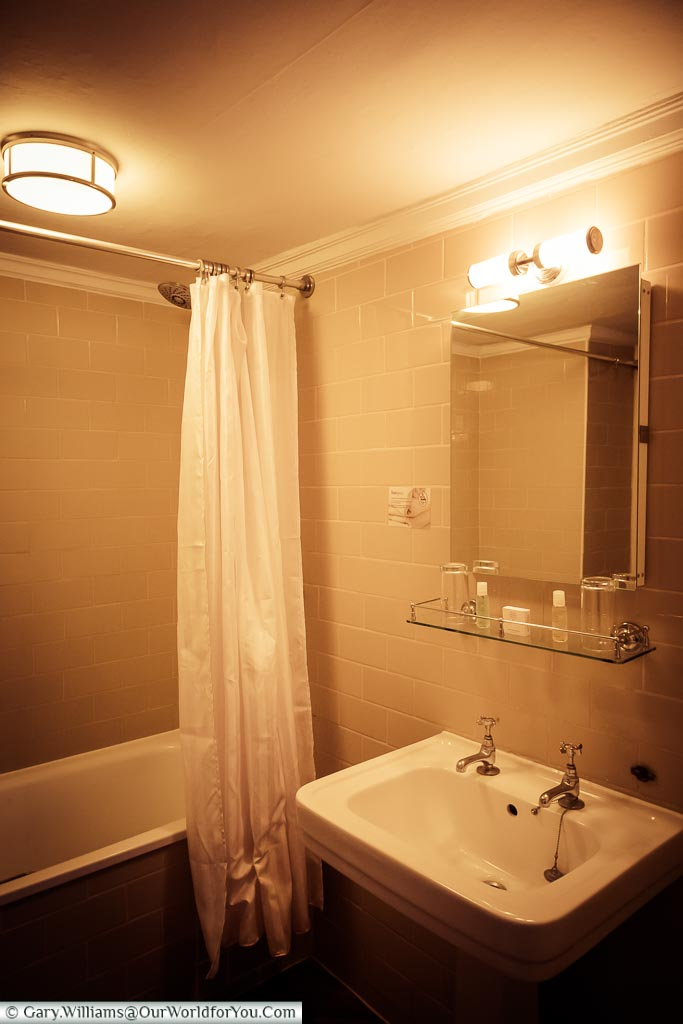 The traditional bathroom in the room featuring a full-size bath and classic styling.