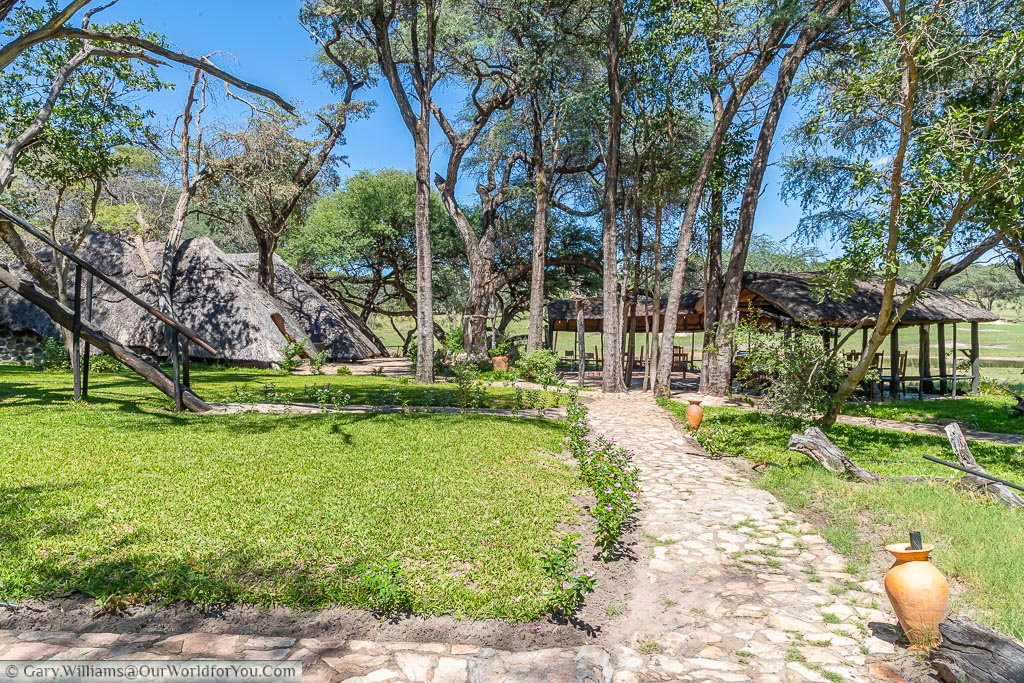 The stone footpath down toward the thatched boma and communal areas between the trees.