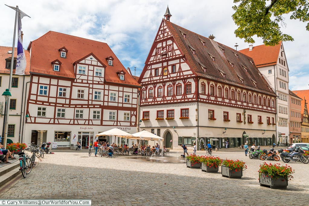 A view of the large, half-timbered, buildings that edge the pedestrianised Marktplatz with its sunken water feature, ice cream shop with tables & chairs outside.