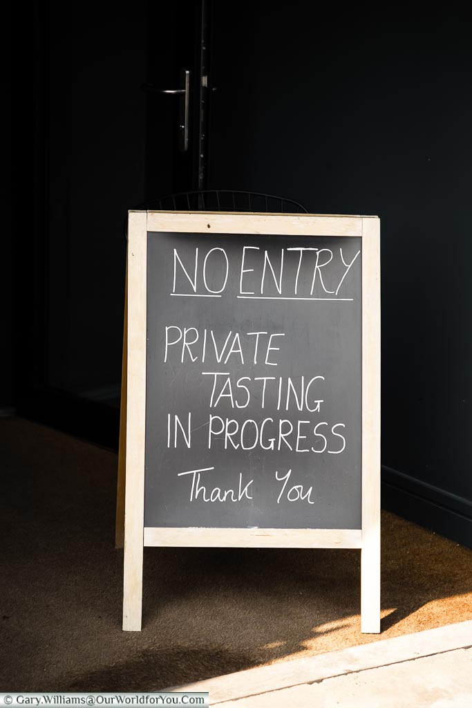 A chalkboard at the entrance to the Wine Sanctuary informing you that wine tasting is in progress.