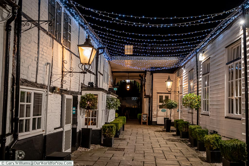 The Inn's courtyard at night, brightly lit by coaching lamps with an additional blanket of lights joining the two sides of the area.