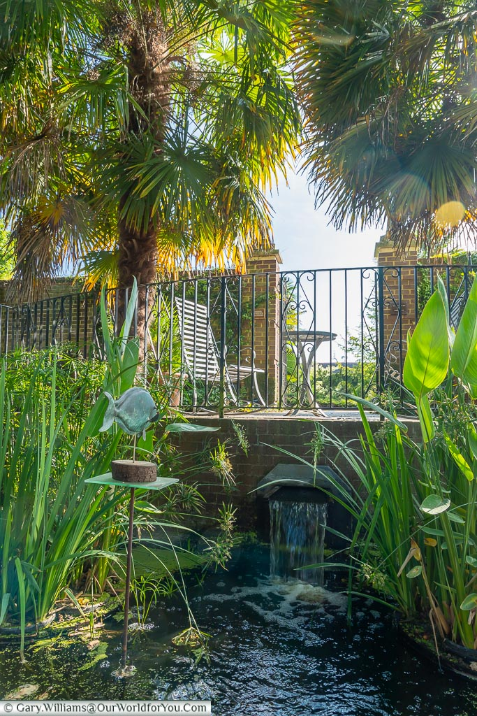 A small pond, fed by a waterfall, below a table and chairs at the exit to the walled garden.