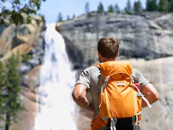35757954 – hiker hiking with backpack looking at waterfall in yosemite park in beautiful summer nature landscape. portrait of male adult back standing outdoor.