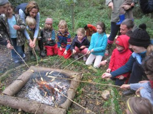 group of children and adults toasting bread over a fire