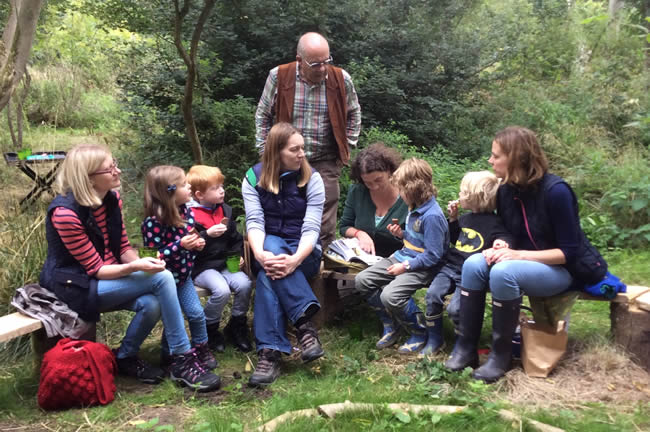 group of adults and children seated on a bench in woodland