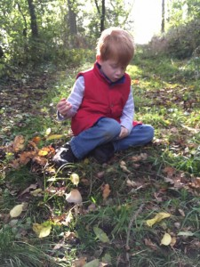 young boy sitting on woodland floor