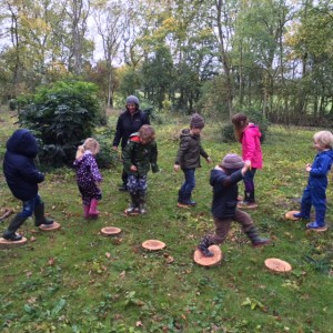 children jumping from one circle of wood to another