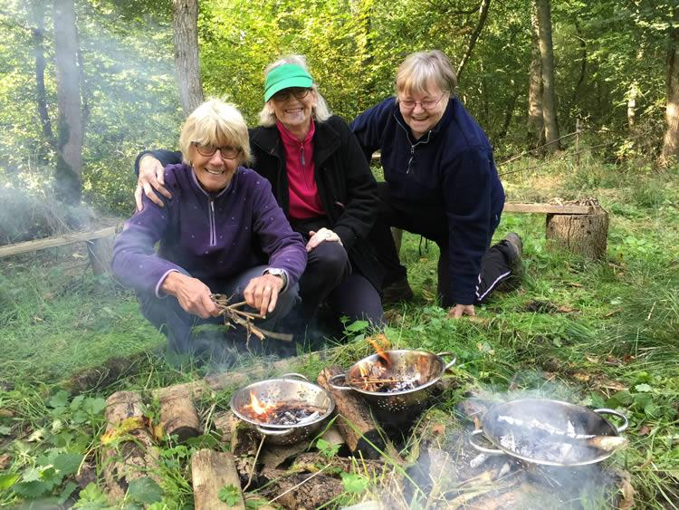 Three ladies making fires in colanders