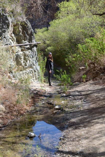 Megan stands by a pipe that was built to carry spring water out of the canyon