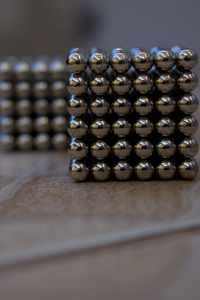 Silver ball magnets attracting each other reflective of the law of attraction