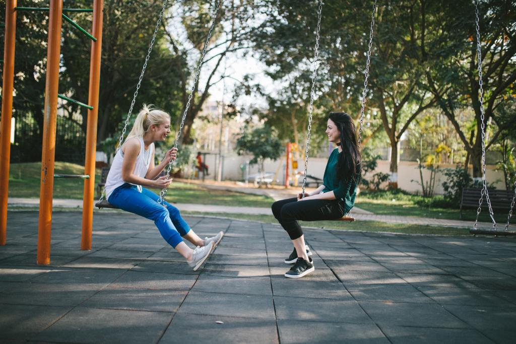 Two women in gym wear on swing talking to show skills you learn with a therapist