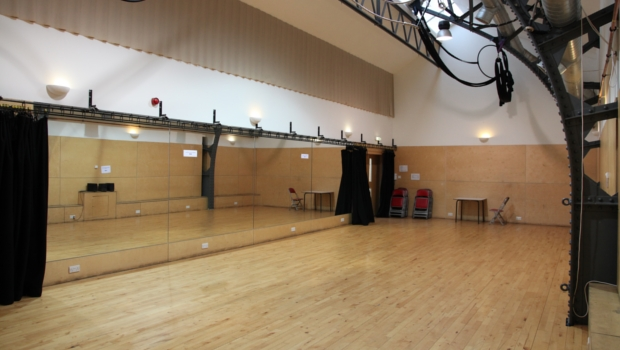 The empty Rehearsal Room at The Out of the Blue Drill Hall has a wooden floor and mirrors, and is ideal for hosting dance and movement classes.