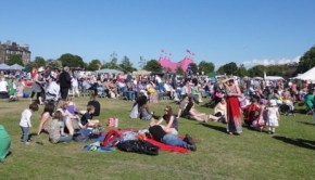 People sit in the sun while Leith Gala Day happens in Leith Links