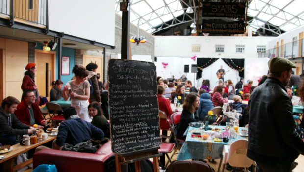 The Drill Hall Arts Cafe Bruncheon lunch menu surrounded by a busy crowd while a guitarist plays in the background
