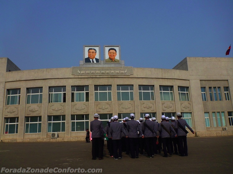 Trabalhadores marchando sob os retratos de Kim Sung-il e Kim Jong-il