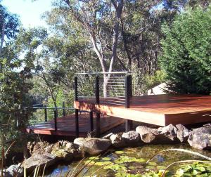 Multi-level timber decking around a bushrock pond