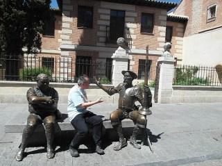 Bankje met koperen beelden van Don Quichot en Sancho Panza met een poserende toerist.