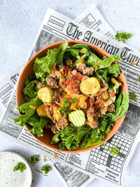 Bunless burger in a bowl of lettuce over newspaper