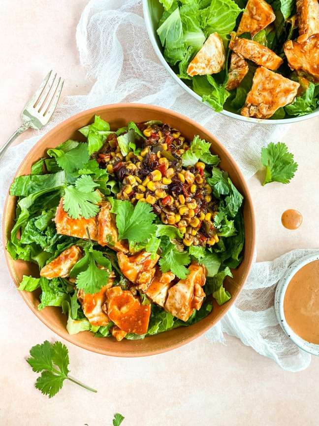 salad bowls with chicken and a pink background