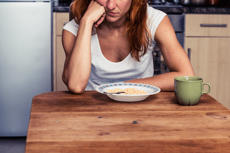 woman sitting at a kitchen table with bowl of cereal, not hungry