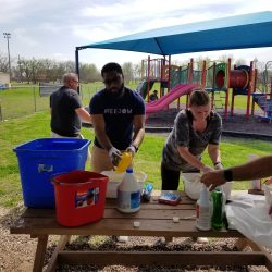 Dell volunteers cleaning play items
