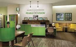 A photo of the welcome desk at a Pearle Vision retail location. A table for consultations and seating in a waiting area are also visible.