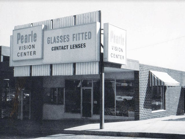 4ef2ecd777d A black-and-white photo of a vintage Pearle Vision corner store. The