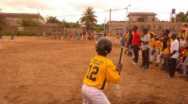 A young batter in a black helmet and yellow baseball uniform stands with his bat, ready for an incoming pitch, on a baseball field in Benin as onlookers and teammates watch.