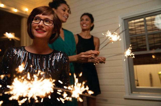 A woman wearing glasses and two out-of-focus women in the background hold sparklers at night on a house's porch.