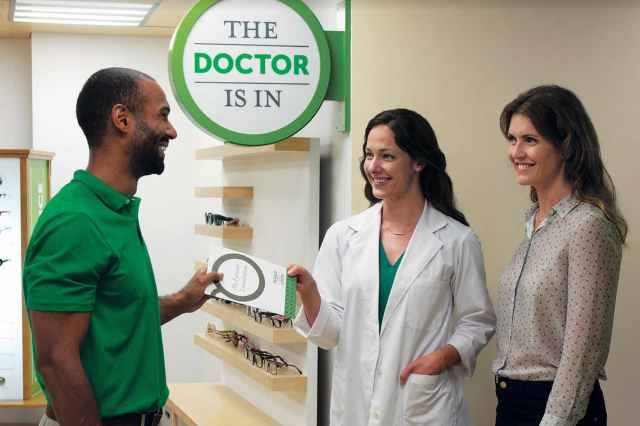 "A smiling doctor hands a brochure to a smiling associate while a smiling customer stands next to them. In the background a sign is visible that reads ""The Doctor Is In."""