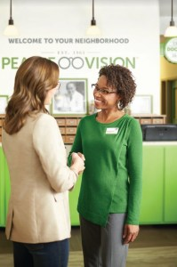 An associate at a Pearle Vision eye care franchise welcomes and shakes hands with a patient.