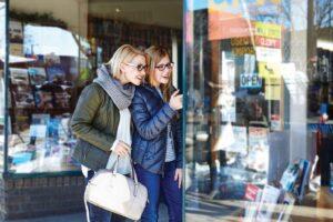 Two women in glasses happily window-shop.