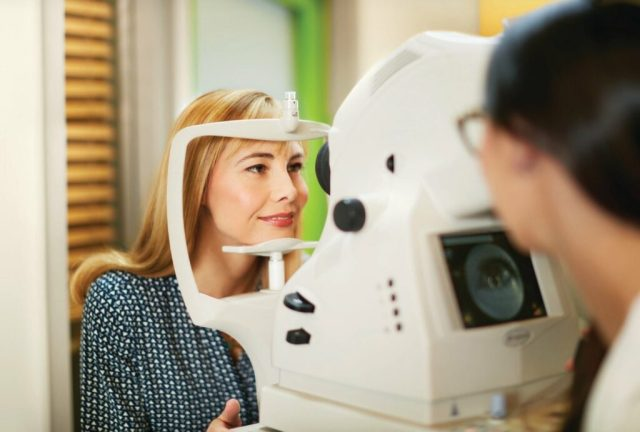 A Pearle Vision patient rests her chin on an eye exam machine; the machine's operator is visible but out of focus in the foreground.
