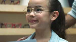little girl in cute glasses with a slight smile