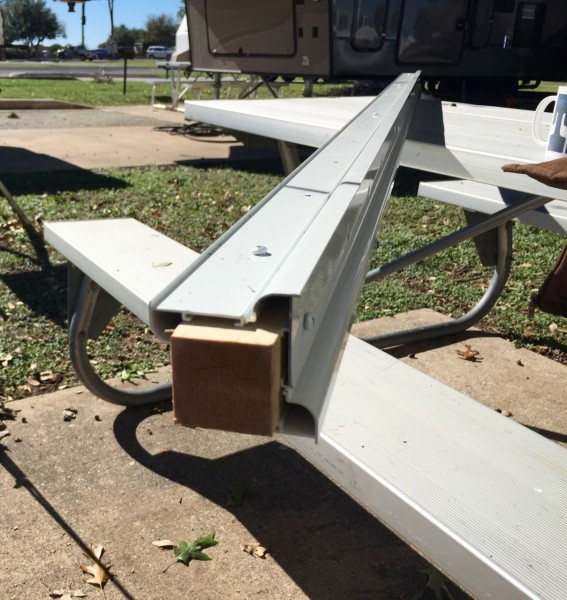 Four lengths of shiny new metal RV gutter, shipped from the manufacturer rather ingeniously fastened to a 6' wooden post.