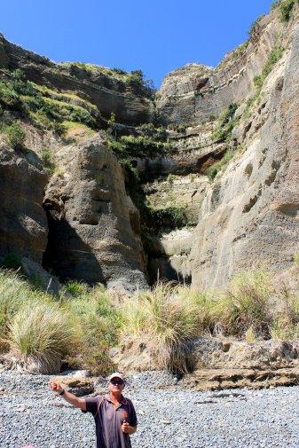 Cape Kidnapper: Erläuterung des Guide am Basin-Gully. Er ist durch fallendes Wasser entstanden, welches vom Wind erfasst und herumgewirbelt wurde, als das Gebiet noch auf Meereshöhe lag (lt. Info von Gannet Beach Adventures)
