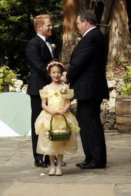 Mitch and Cam at their wedding in Modern Family -- the Pluto in Libra sit-com.
