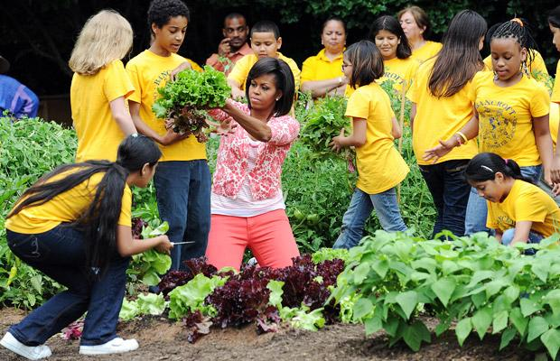 Michelle Obama exemplifying her generation. She had her first child at 32. Her firs act in the White House was to plant an organic garden, and her she is kneeling and holding a lettuce.