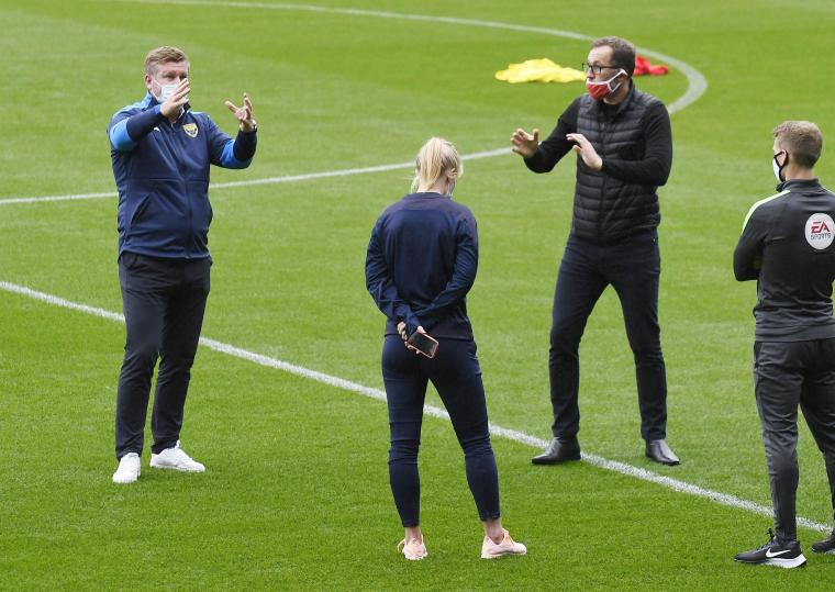Crewe Alexandra boss David Artell (in red face mask) talks with Oxford United boss Karl Robinson (left), U's physio Amy Cranston (second left) and referee Will Finnie   Picture: David Fleming