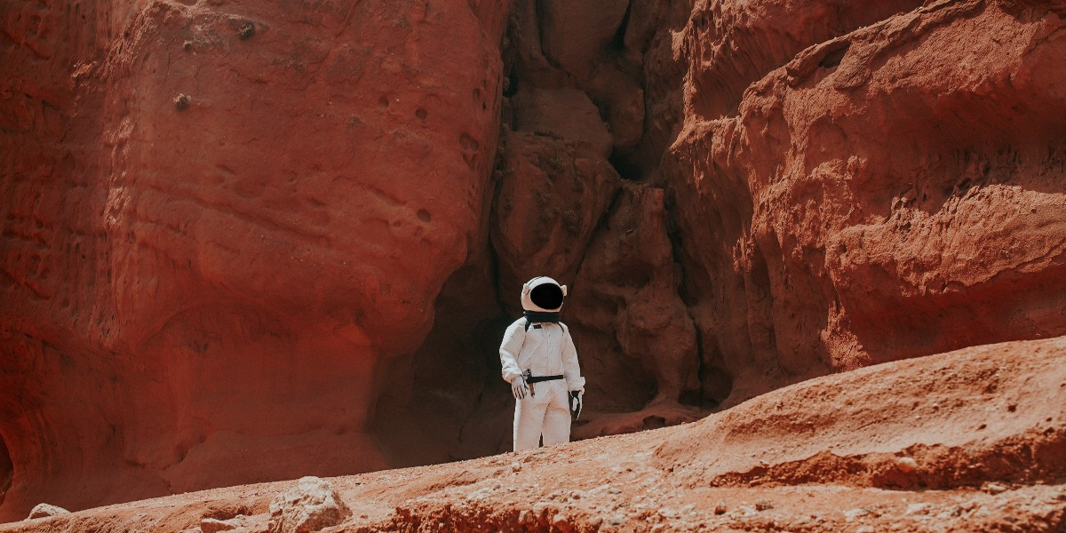A person dressed in a spacesuit standing in front of some cliffs.