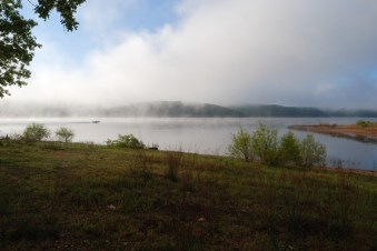 Mist and low clouds wafting over Truman Lake in the morning while the sun breaks through, lighting the shore. A motorboat speeds by.
