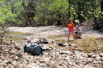 A teen girl standing in the water helping a man with the camp chore of filtering water from Piney Creek during a spring backpacking trip in the Ozarks.