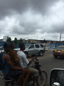 An Okada driver transporting 2 passengers on a cloudy day in Lagos