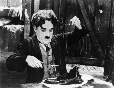 "01 Jan 1925 --- Charlie Chaplin eating a shoe in the classic scene from the ""The Gold Rush,"" 1925. Movie still. --- Image by © Bettmann/CORBIS"