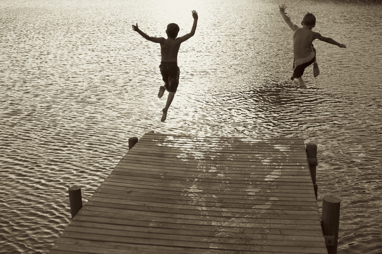 Two Boys Diving off Dock into Lake --- Image by © Royalty-Free/Corbis