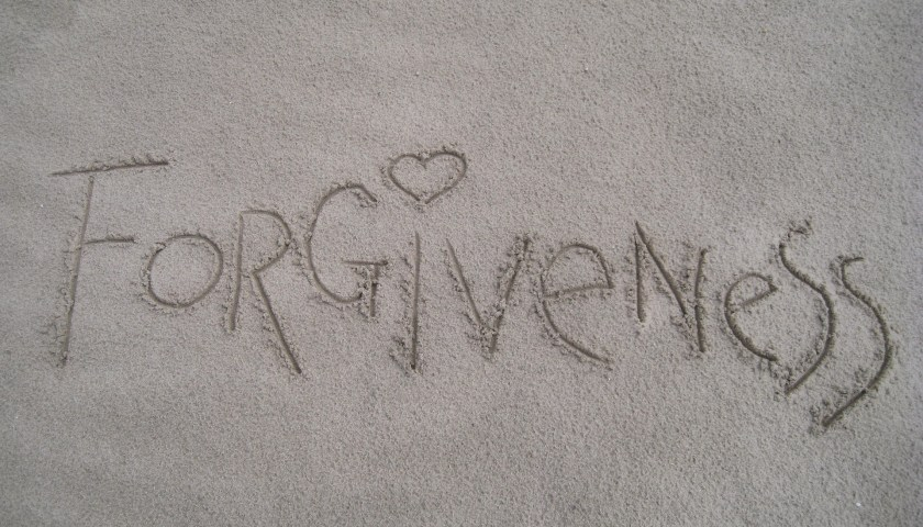 """""""forgiveness"""" written in sand with a heart for the dot over the """"i"""""""