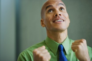 Mixed race businessman smiling with fists clenched
