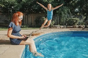 mom working administrative job from home pool with daughter