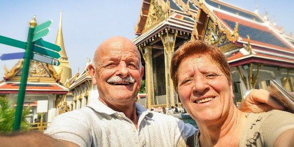 a happy expat couple taking a selfie outside a thai temple as they enjoy their retirement in thailand